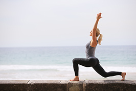 Caroline Pearce doing Yoga pose with ocean in background